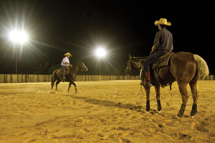 Non-pro rider Parke Greeson watches as Boyd works with Greeson's horse.