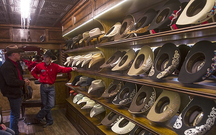 A customer shops for a lid in the JW Brooks Custom Hat booth.