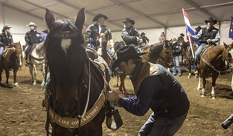 NFR roper Jade Corkill tightens his cinch before riding in the grand entry.
