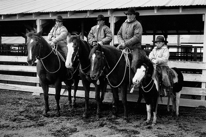 Bryan Neubert (second from right) taught his children (from left) Kate, Jim and Luke, to focus on a horse's good traits.