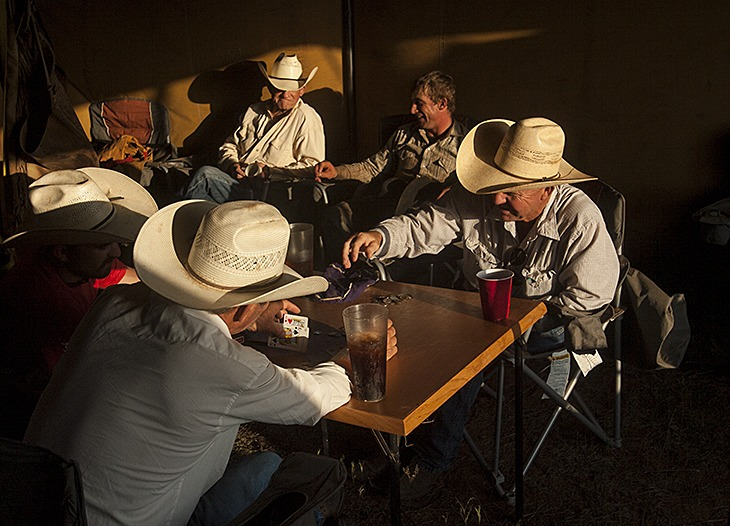 Wagon boss Reggie Hatfield (right) plays poker with his men under the wagon fly.