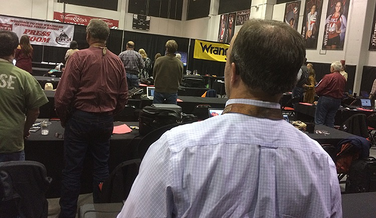 Members of the media covering the NFR pause during the National Anthem.