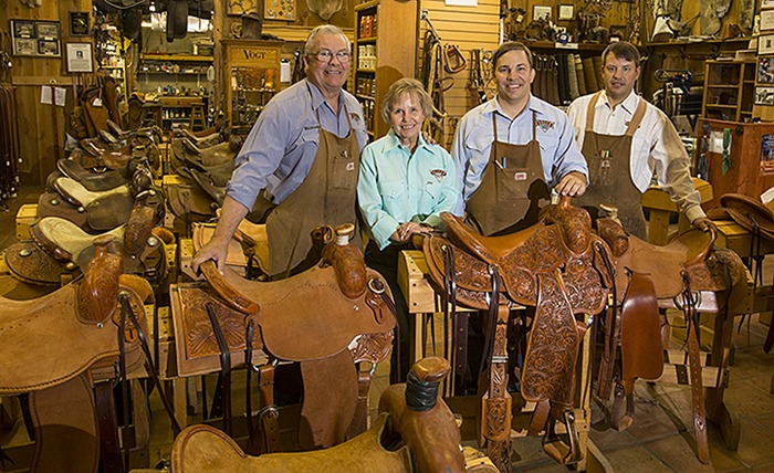 Richard Oliver and family standing by saddles