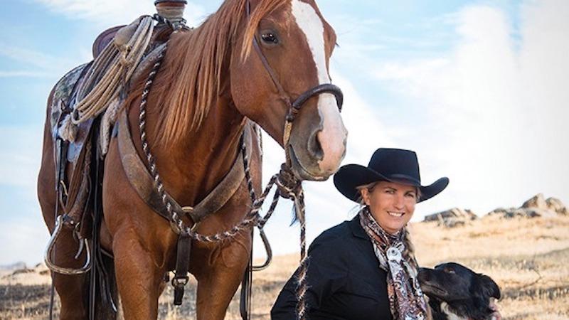 Diana Bohna sitting with dog next to horse