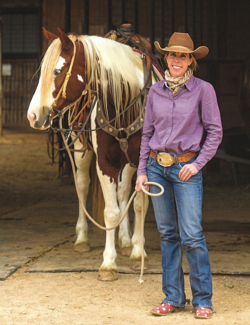 Kellie Neubert standing with paint horse