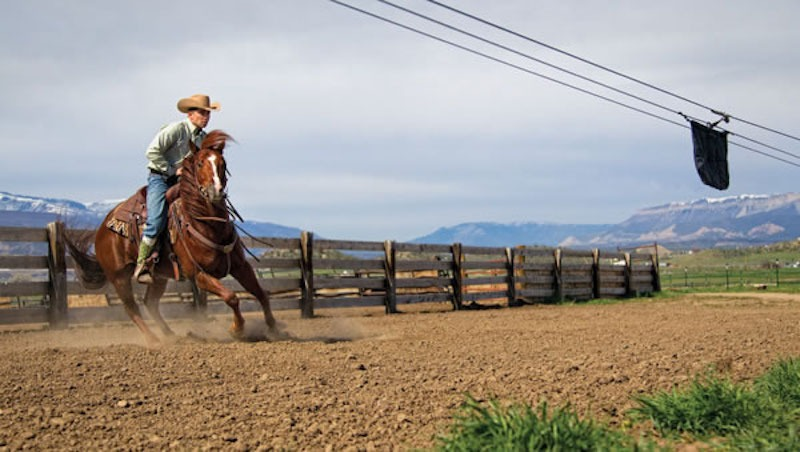 Aaron Ralston works his horse on a flag.