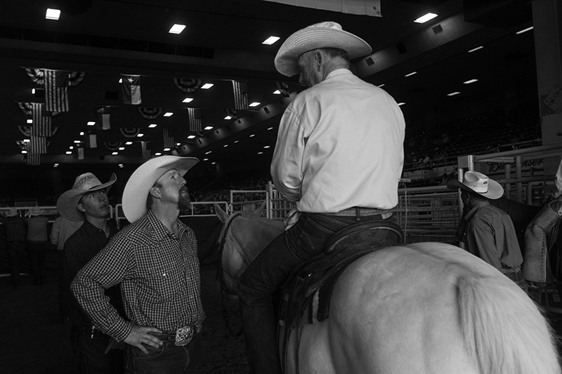 Cowboys visiting about a horse.