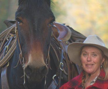 Wanda Wilcox standing by a mule