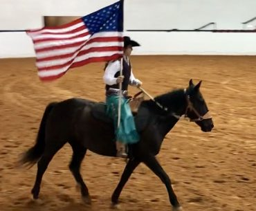 Shelby Crider riding mustang Pearl carrying American flag