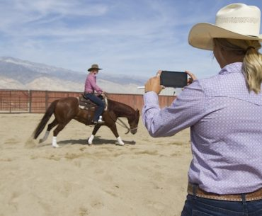 Cowgirl taking video of girl on horse