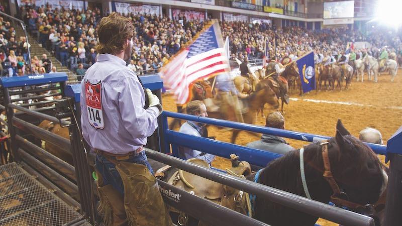 Tyler Bridges standing behind bucking chutes during national anthem