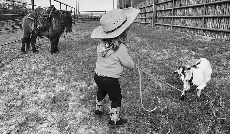 kid tying up a goat with pony