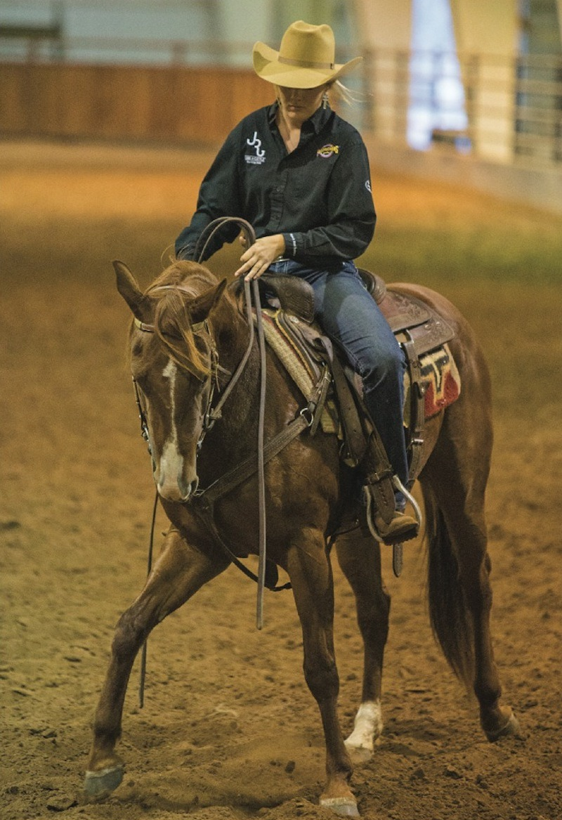 Texas Tech ranch horse team member demonstrating using hand and leg cue while horseback