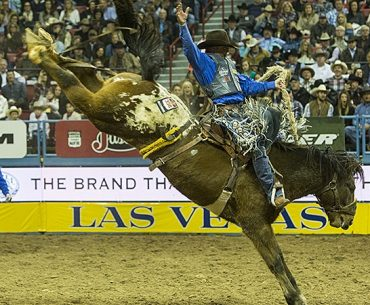 Cort Scheer riding a saddle bronc horse at the NFR