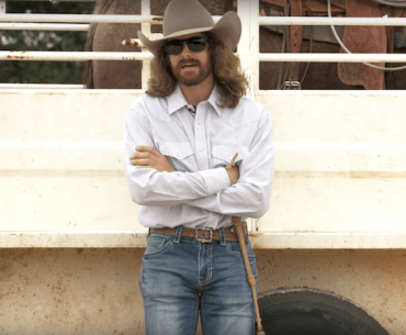 Dale Brisby leaning up against horse trailer