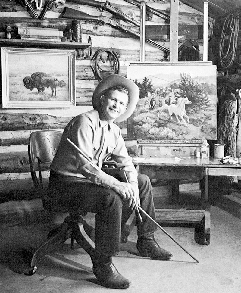 George Phippen sitting next to paintings