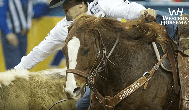 Tyler Pearson jumping off AQHA horse of the year Scooter at the NFR