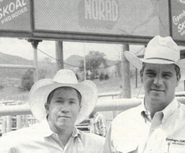 Randy Barnes and Steve Scribner standing in front of rodeo scoreboard