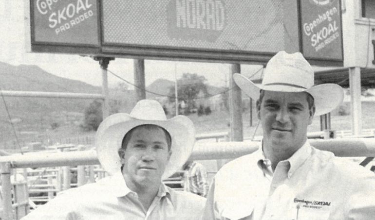 Randy Barnes and Steve Scribner standing in front of rodeo scoreboard