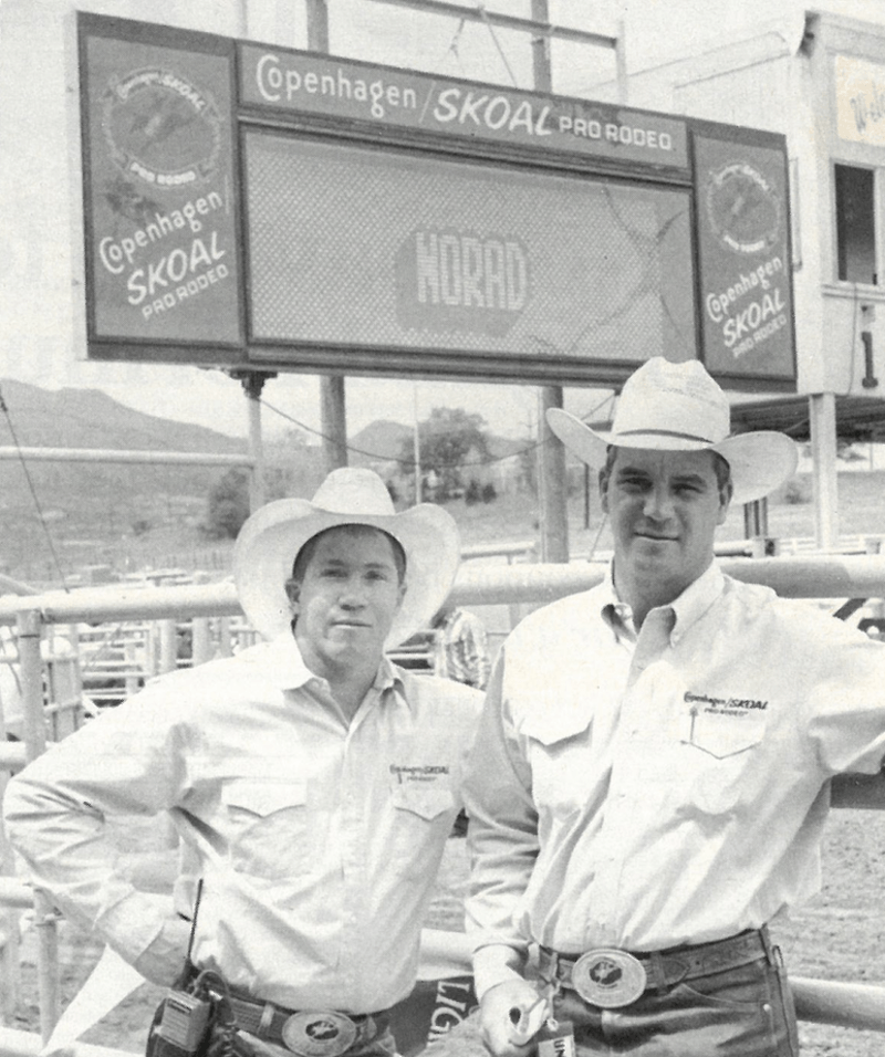 Randy Barnes and Steve Scribner standing in front of the rodeo scoreboard