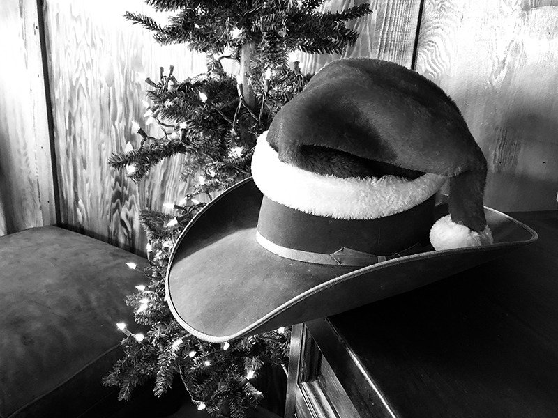 cowboy hat with santa hat on top