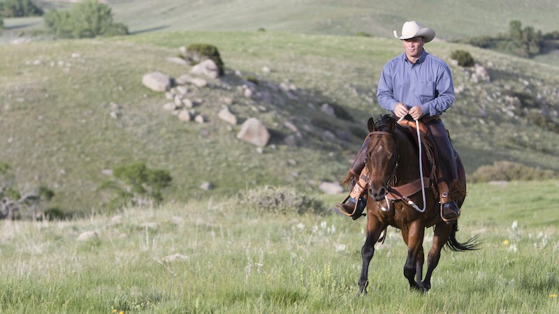 Ken McNabb riding a horse through rocky pasture