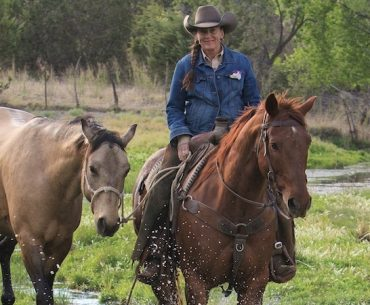 Missy Cantrell riding a horse and ponying another