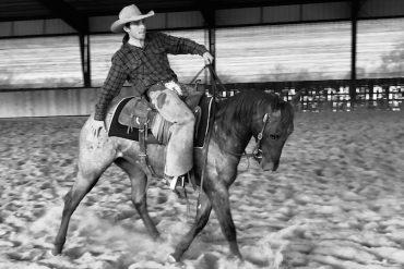 Luke Neubert riding a colt and touching it's hind end