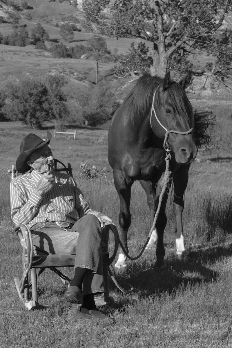 Bill Hackett sitting in rocking chair holding on to horse standing next to him.