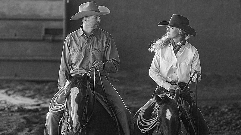 husband and wife riding horses next to each other