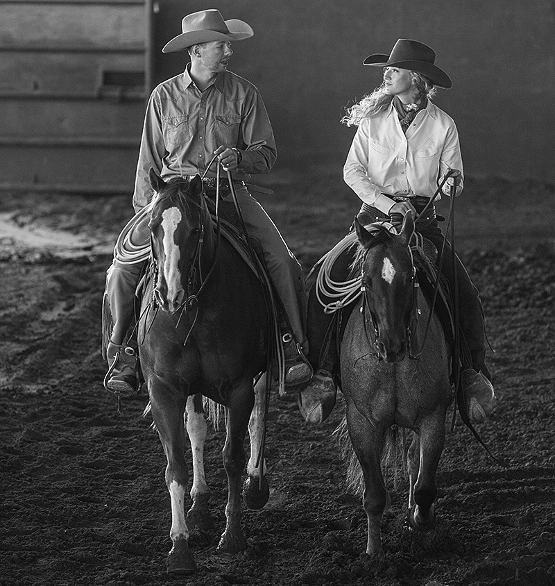 husband and wife riding horses next to each other in an arena