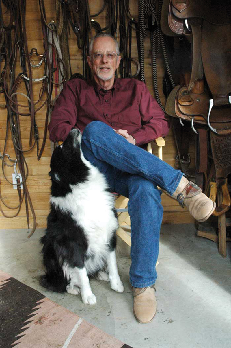 Don Weller sitting in a chair with dog, Buster.