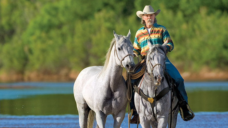 buck taylor riding horses in water