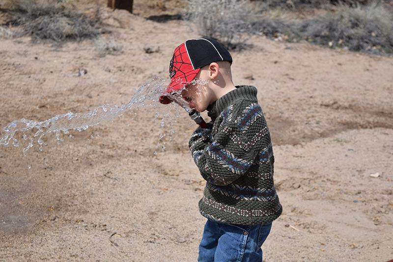 boy drinks water from garden hose