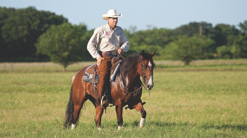 Kory Pounds riding horse through green pasture