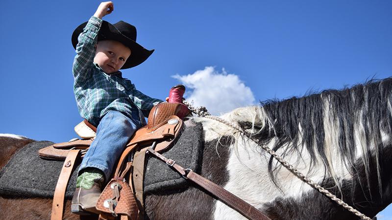young cowboy rides horse