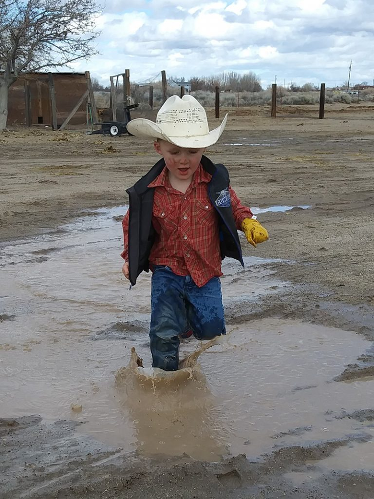 little cowboy stomps through mud puddle