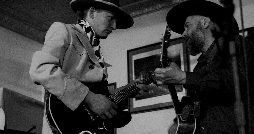 Justin Reichert and Ira G play guitar