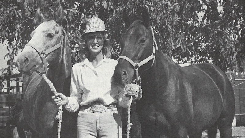 Edie Roer standing with two horses