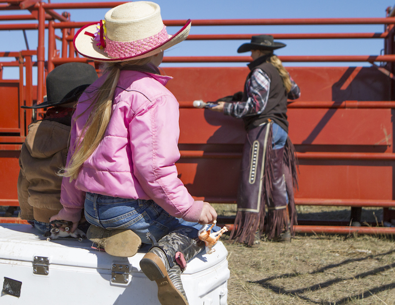 Eng kids sitting on a cooler watching their mom work the chute