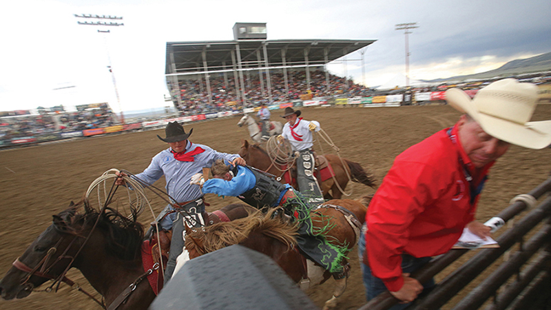 pick-up men grab bronc rider at National High School Finals Rodeo
