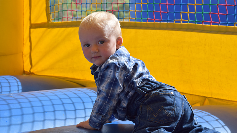 baby boy in bounce house at rodeo