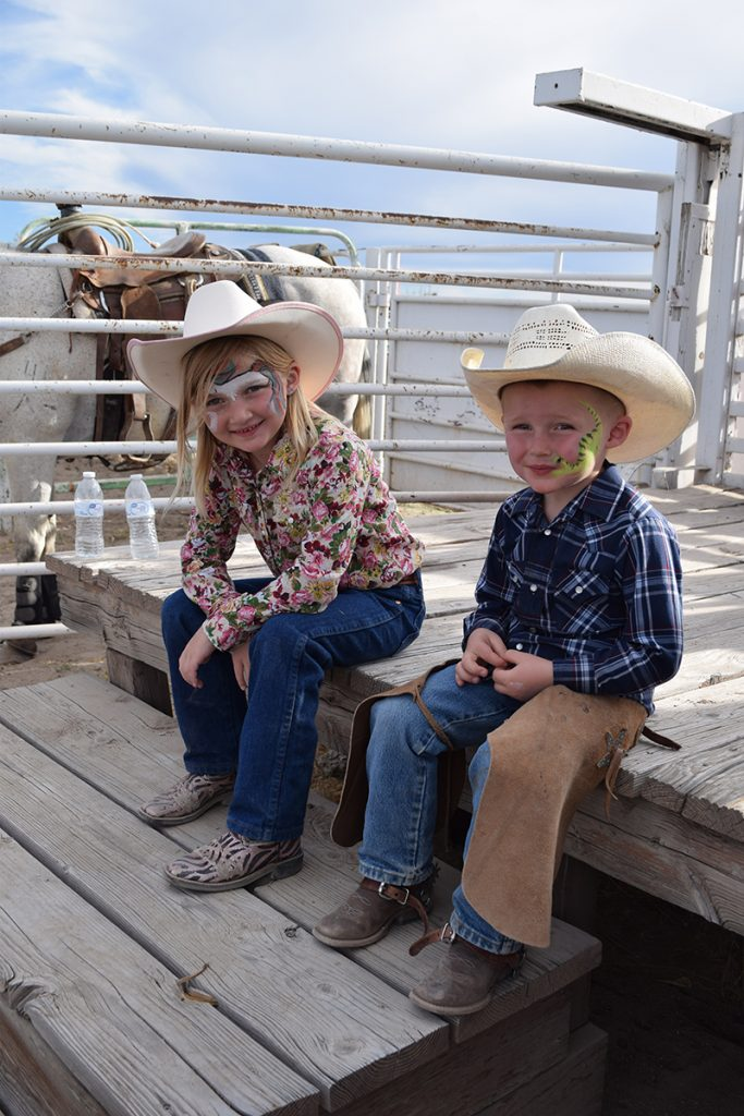 cowboy and cowgirl with faces painted at the rodeo