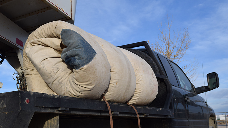 rolled bedroll on a flatbed pickup truck