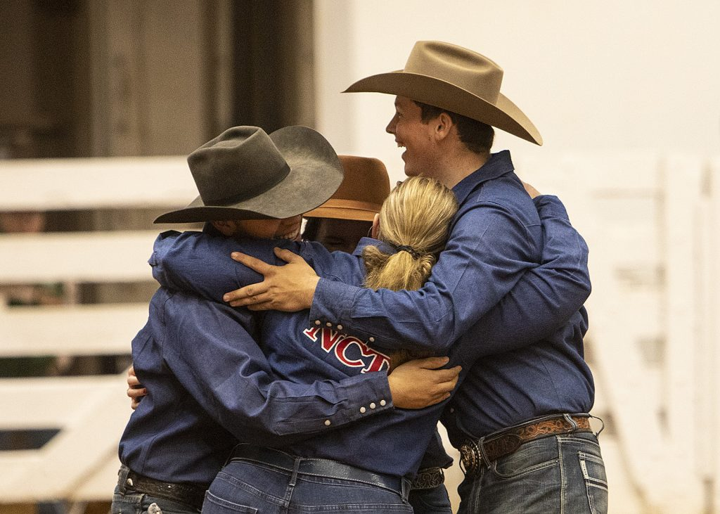 The university team celebrated with hugs.