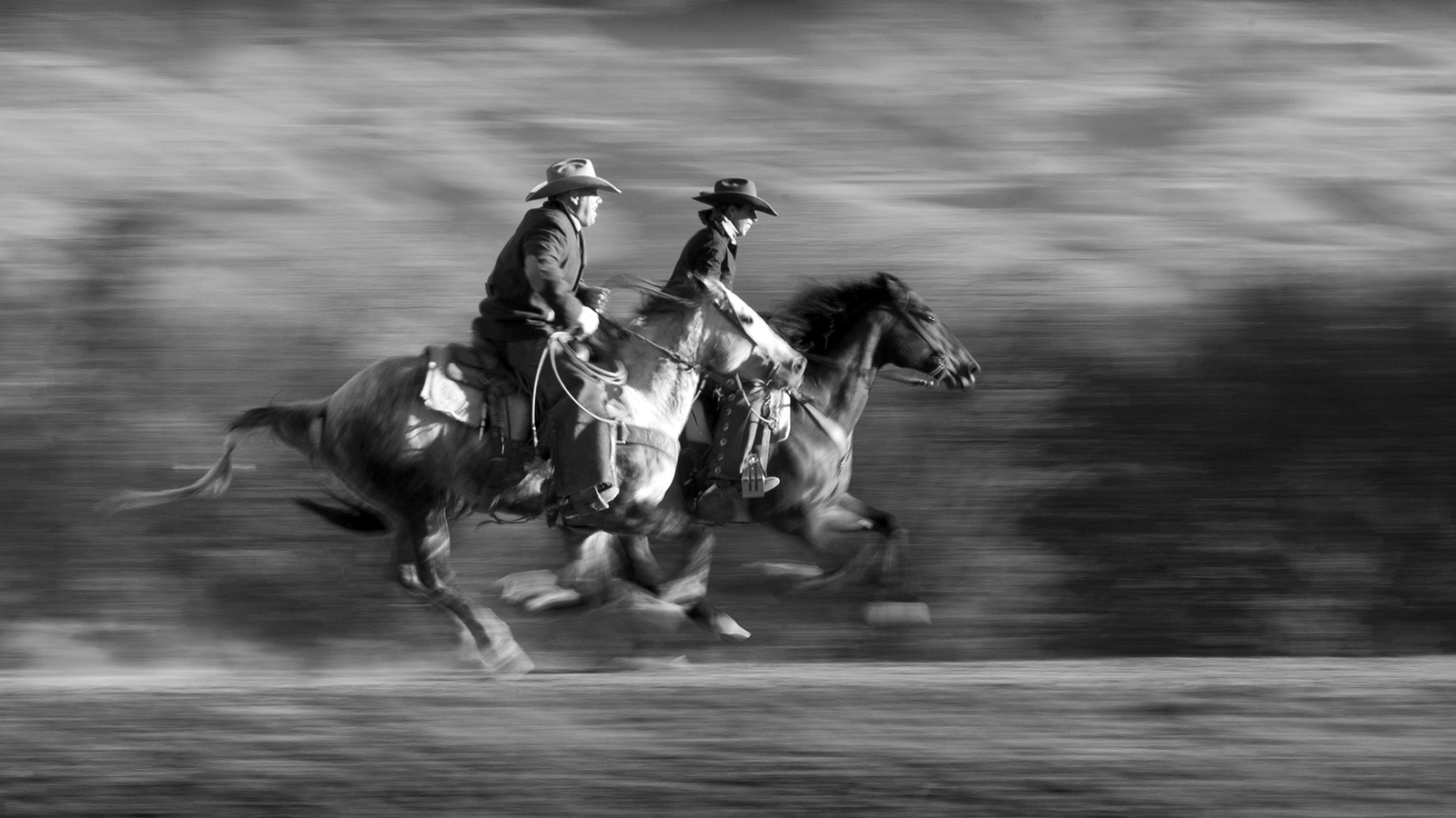 Two riders gettin' it at a gallop.