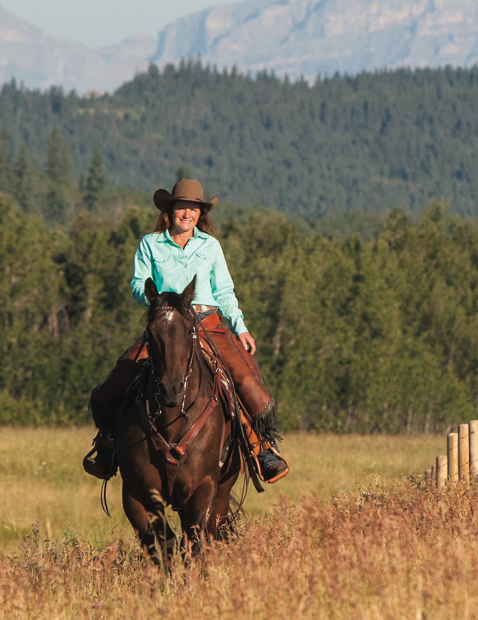 Mary Beth Sibbald riding horse through Alberta pasture