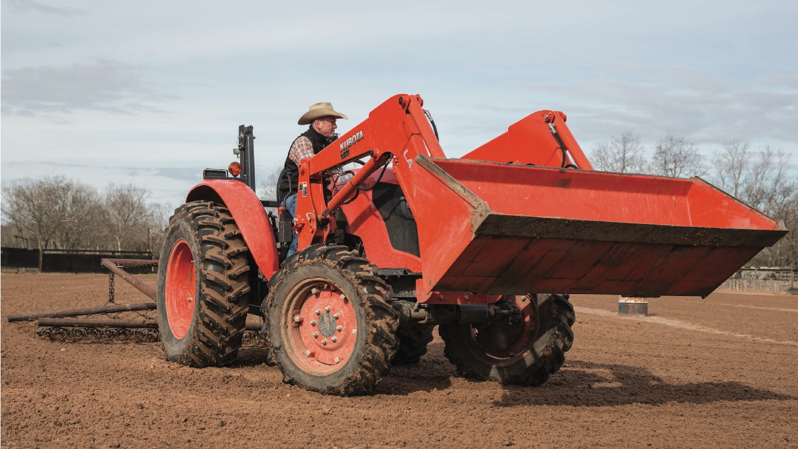man on tractor with ranch equipment