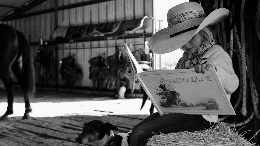 A young cowgirl learns to read a Western book