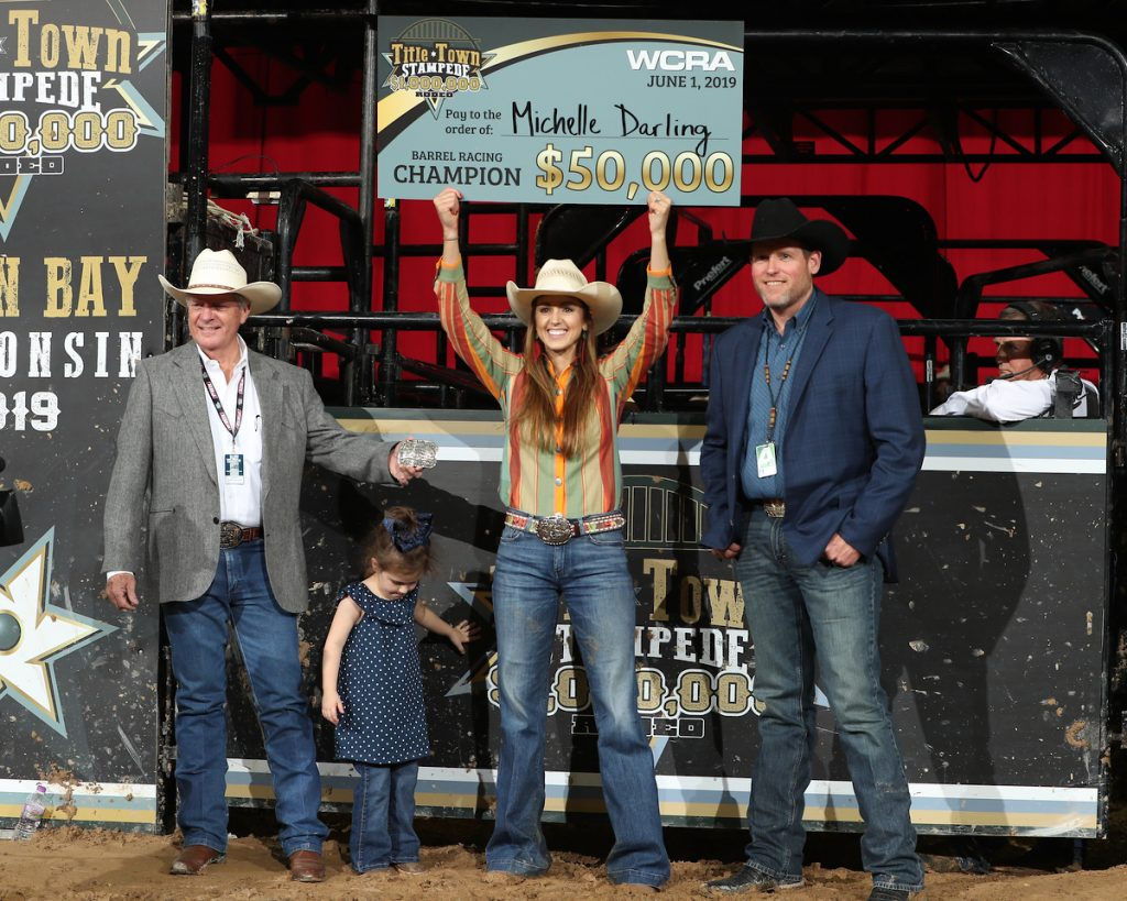 Michelle Darling holding up a check from the Green Bay WCRA